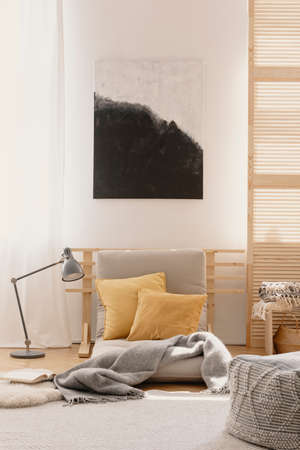 Abstract painting on the white wall of japanese inspired bedroom design with beige futon and yellow pillows Stock Photo