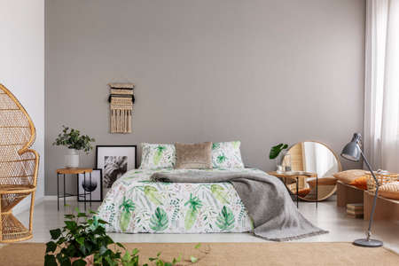 Real photo of double bed with leafy sheets placed in bright bedroom interior with macrame on the wall, mirror and posters on the floor and fresh plants Фото со стока