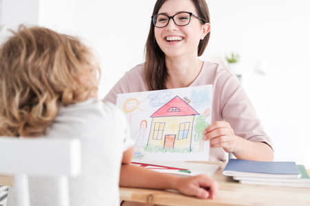 Smiling psychologist with home picture and child in a family support centre Stock Photo