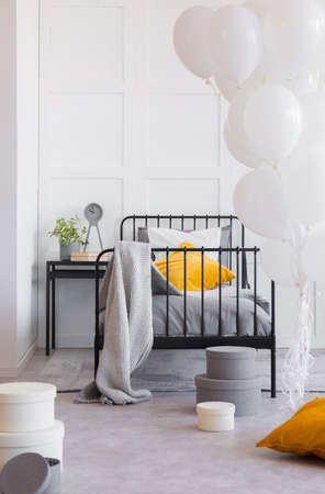 Blanket and orange pillow on bed next to table with plant in bedroom interior with balloons. Real photo Stock Photo