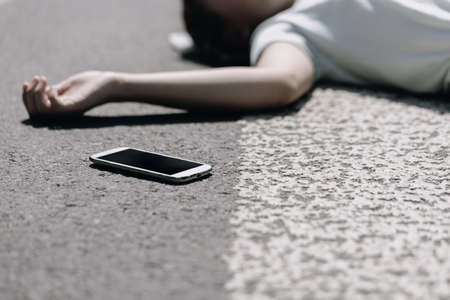 Smartphone and careless victim of traffic accident lying on a crosswalk