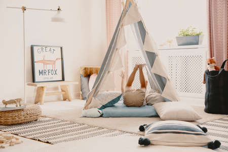 Child in tent in bright playroom interior with fox poster on wooden stool next to lamp. Real photo