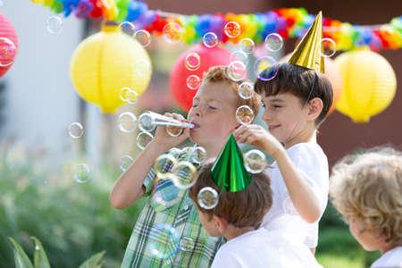 Fröhliche Jungs mit bunten Hüten, die Seifenblasen während einer Geburtstagsfeier im Freien machen Standard-Bild