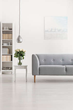 Vertical view of grey comfortable sofa in white living room interior with oil painting on the wall and luxury silver lamp above vase with white roses, real photo with copy space and mockup Imagens