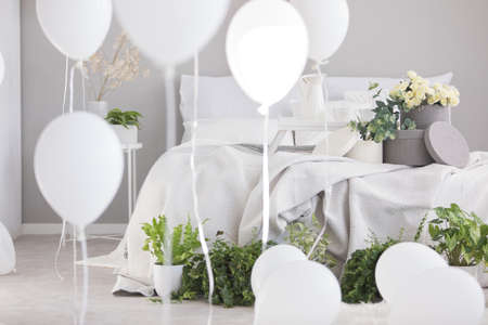 Flowers and green plants on bed with blanket in grey bedroom interior with white balloons. Real photo