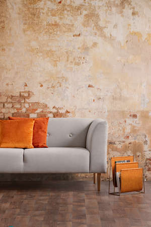 Orange cushions on grey sofa against red brick wall in modern living room interior. Real photo Stock Photo
