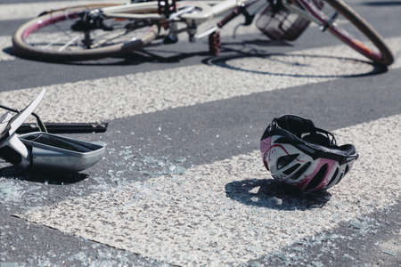 Child's helmet and car's mirror on a pedestrian crossing after collision with a bike Banque d'images