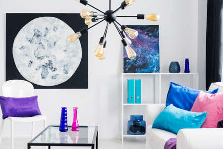 Lamp above table and white sofa with pink and blue cushions in flat interior with posters. Real photo