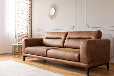 Real photo of a leather couch in a living room interior