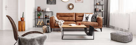 Real photo of brown leather couch with blanket and pillows standing in bright living room interior with fresh plant, candles and decor on metal racks, coffee table with tea cup and book and window with drapes