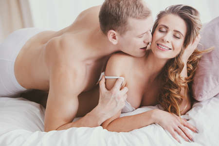 Naked man kissing smiling womans neck during sensual foreplay in the bedroom Stock Photo