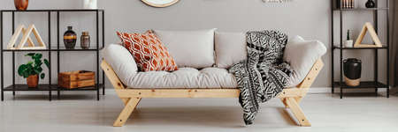 Light grey sofa with patterned pillow and black and white blanket in real photo of scandi living room interior with metal racks with decor Stock Photo