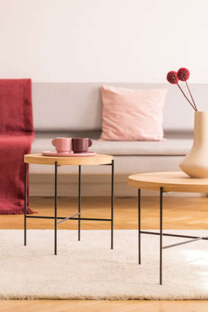 Coffee tables with coffee cups and vase with flowers in bright living room interior with grey sofa, real photo with copy space on the empty white wall Stock Photo
