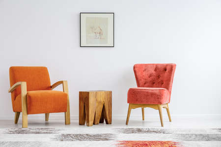 Poster on white wall with copy space in trendy living room interior with retro armchairs and wooden coffee table