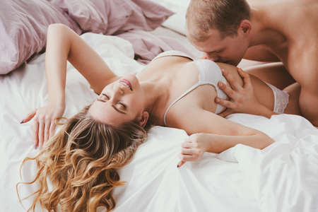 Smiling woman wearing underwear during sensual foreplay with husband kissing her 版權商用圖片