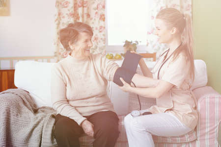 Smiling doctor measuring pressure of happy senior woman at home Stock Photo