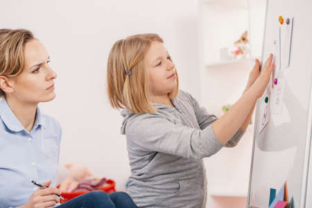 Smiling girl doing exercises during meeting with concentrated psychotherapist Stock Photo