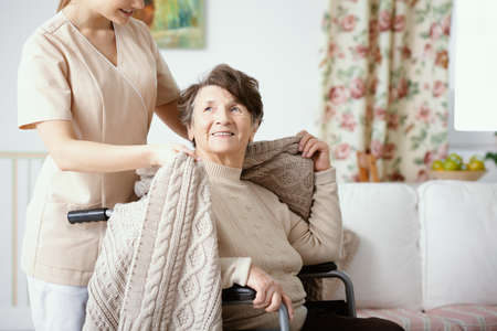 Nurse helping smiling elderly woman in the wheelchair during home visit