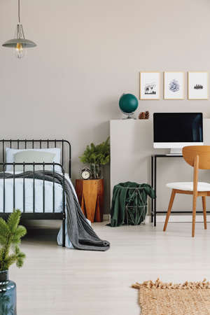 Single metal bed with blue bedding next to wooden nightstand and desk with computer, real photo with copy space on the empty grey wall Stock Photo