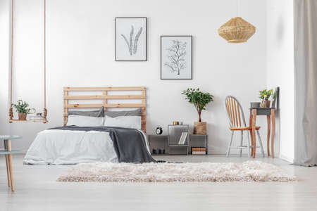 Minimal posters in black frames on white wall of classy Scandinavian bedroom interior with elegant dresser and warm carpet Stock Photo