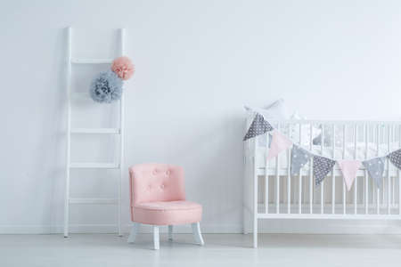 Elegant kids room with white wooden ladder and crib with star shape pillows, copy space on empty white wall