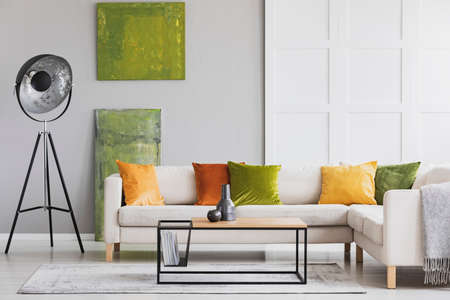 Pillows on corner sofa next to lamp in living room interior with green posters and table. Real photo Stock Photo