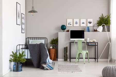 Bright grey bedroom interior with workspace with desk and computer, real photo with copy space on the empty wall