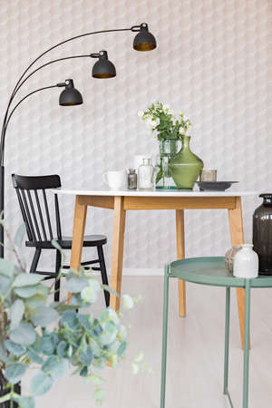 Elegant dining room with round table with vases and flowers next to black wooden chair and industrial metal lamp, real photo with unique wallpaper Stock Photo