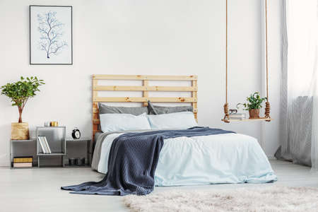 Bright bedroom interior with king size bed with light blue bedding and warm blanket, copy space on white wall