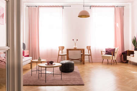 Dining table with chair in the middle of bright pastel pink living room in tenement house Stock Photo