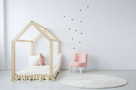 Pastel pink armchair next to wooden house shape bed with toy and blanket, copy space and golden stars on empty white wall