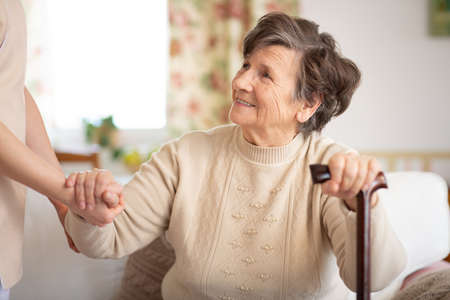 Caregiver holding hand of smiling senior woman with walking stick