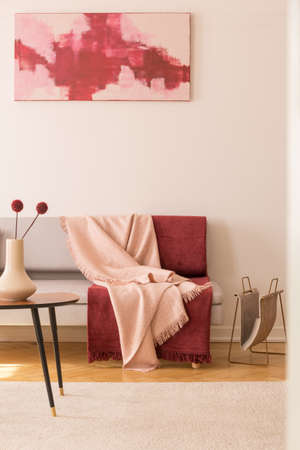 Abstract painting on the empty white wall of elegant living room with grey couch with pastel pink and burgundy blankets Stock Photo