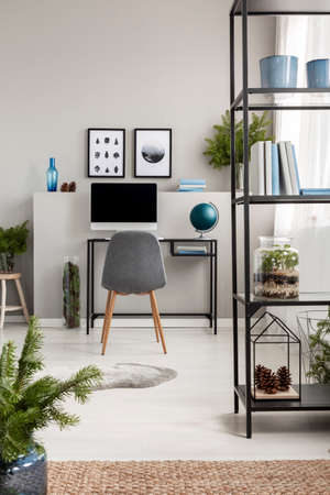 Metal shelf with books in elegant home office interior with computer on desk and graphics on the empty grey wall
