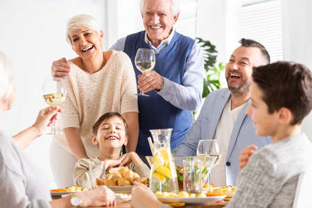 Smiling grandfather making toast during family dinner with happy boy and parents Stock Photo