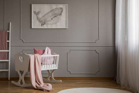 Whale on poster on the empty grey wall of cute baby bedroom interior with white cradle with pillow and paste pink blanket Stockfoto