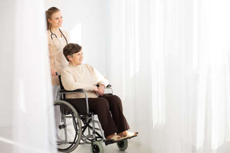 Smiling nurse supporting sick elderly woman in the wheelchair next to copy space
