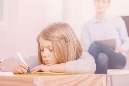 Concentrated girl holding pen while doing exercises during extra-curricular classes