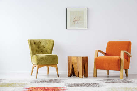 Olive green stylish armchair next to wooden coffee table and orange vintage armchair in tasteful living room interior with camel poster on white wall