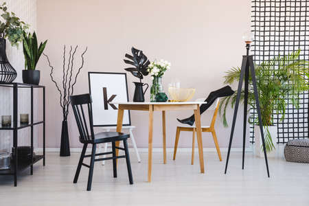 Stylish dining room with round wooden table and comfortable black and white chairs, real photo with copy space on the empty wall and poster on chair