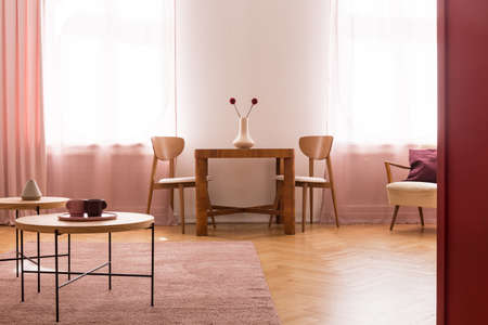 Chairs at wooden table with stylish vase with flowers in bright dining room interior with coffee tables on pink carpet