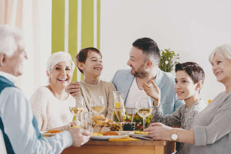 Happy boy between parents during family dinner with smiling grandmother