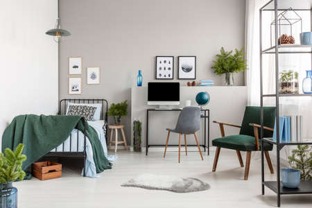 Retro dark green armchair in stylish bedroom interior with single metal bed and desk with computer Stock Photo