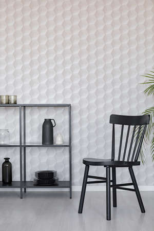 Black wooden chairs next to metal shelf with vases, plate and accessories on empty wall wall with unique wallpaper, real photo with copy space