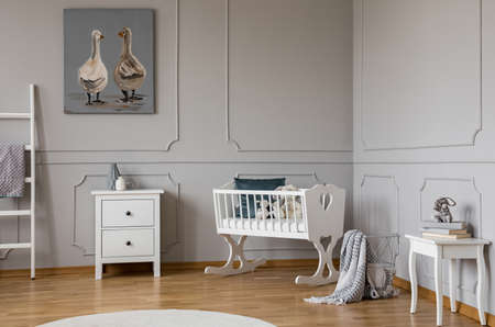 White wooden cradle with emerald pillow and toys in the corner of stylish scandinavian baby bedroom interior, real photo with copy space on the empty wall Stock Photo