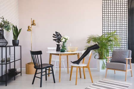 Black mannequins leg on wooden chair in elegant dining room interior with round wooden table, metal shelf and retro armchair, real photo with copy space