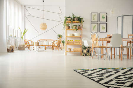 Patterned carpet on white wooden floor in sophisticated living and dining room interior with rattan sofa and armchairs and wooden table with fancy chairs