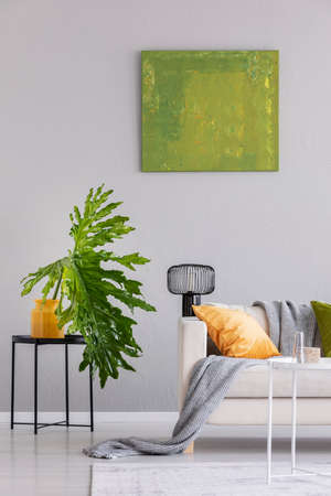 Plant on table next to settee with lamp and blanket in grey loft interior with green poster. Real photo