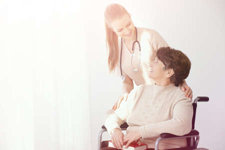 Smiling nurse supporting paralysed elderly woman in the wheelchair next to copy space Stock Photo