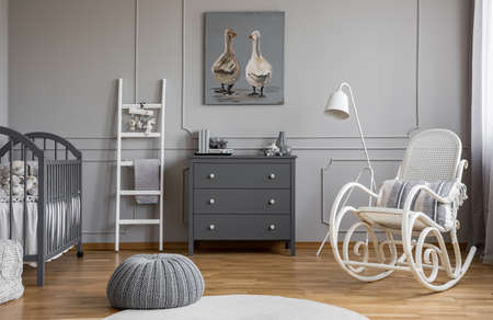 Grey pouf on white carpet inelegant baby bedroom interior with white and grey furniture, real photo Stockfoto